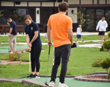 Boy and girl playing miniature golf